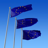 three-flags-europe-union-against-blue-sky-18418345